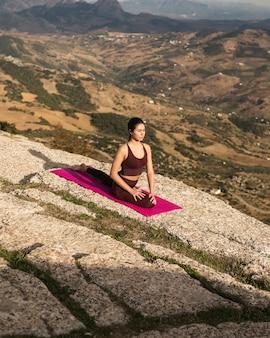 Alto ángulo hembra joven en pose de yoga
