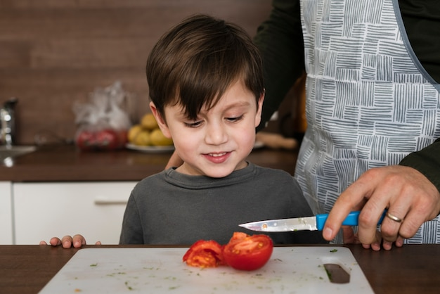 Alto ángulo hijo en cocina con padre