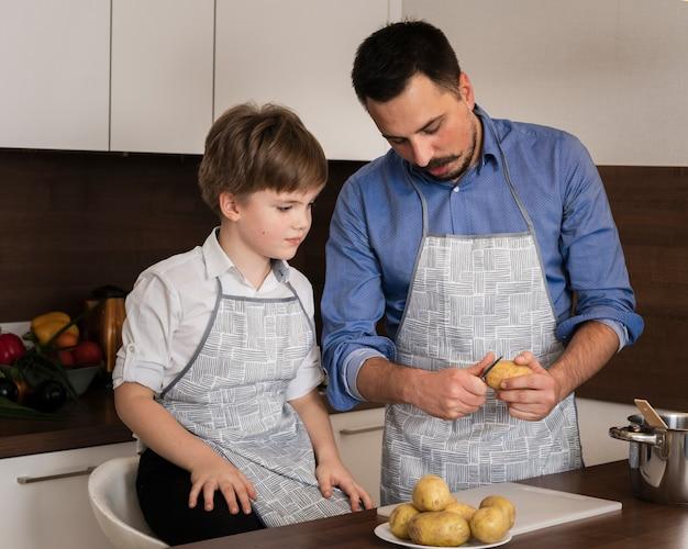 Alto ángulo hijo y papá limpiando papas