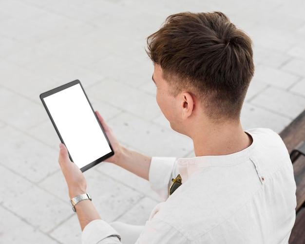 Alto ángulo de hombre mirando tableta al aire libre