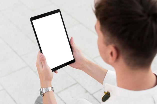 Alto ángulo de hombre mirando tableta con espacio de copia