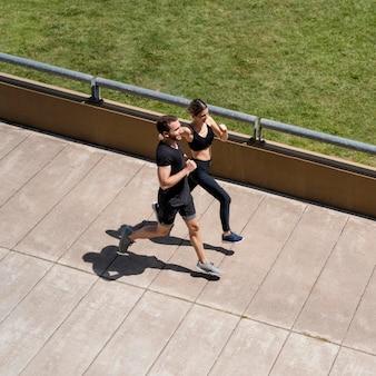 Alto ángulo de hombre y mujer corriendo juntos al aire libre
