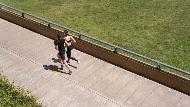 Alto ángulo de hombre y mujer corriendo juntos fuera