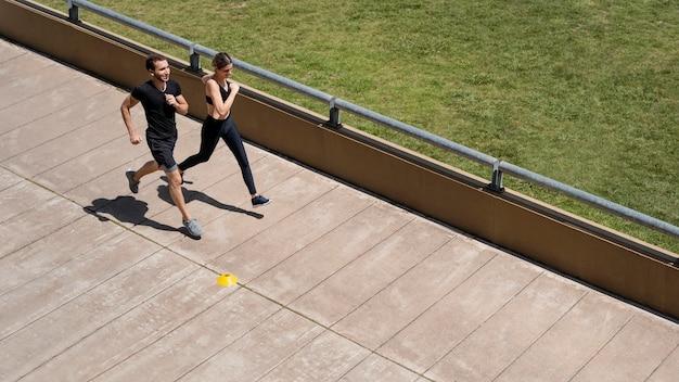 Alto ángulo de hombre y mujer corriendo juntos
