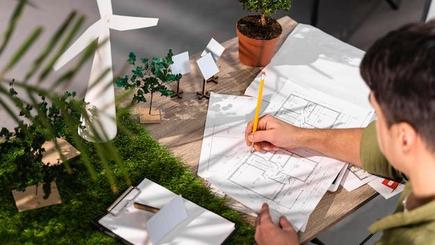 Alto ángulo del hombre que trabaja en un proyecto de energía eólica ecológica con planes en papel