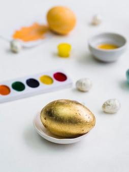Alto ángulo de huevo de pascua dorado con paleta desenfocada