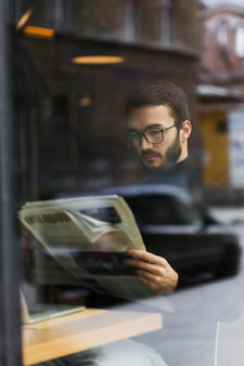 Alto ángulo joven mal e leyendo periódico