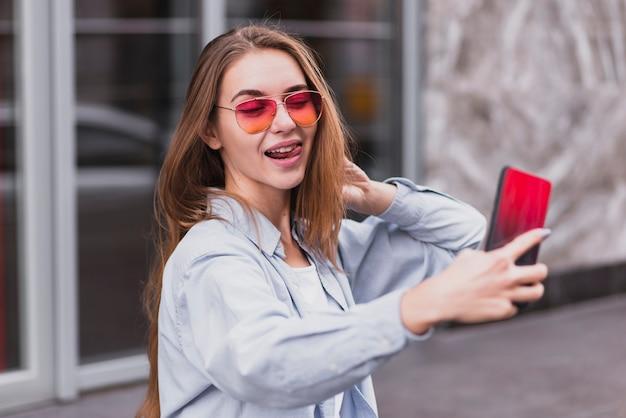 Alto ángulo juguetón hembra tomando selfies