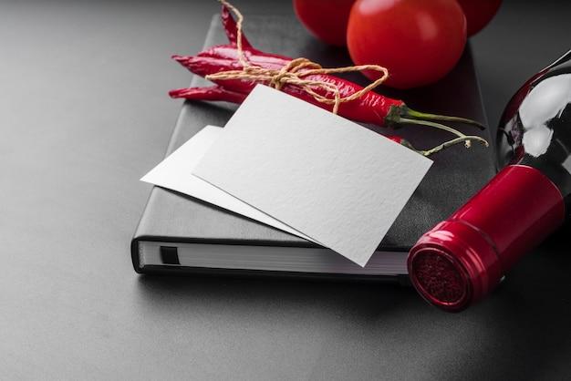 Alto ángulo del libro de menú con botella de vino y chiles