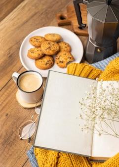 Alto ángulo de libro sobre suéteres con taza de café y galletas