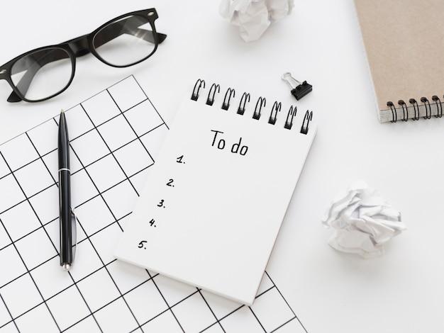 Alto ángulo de la lista de tareas en el bloc de notas con gafas y bolígrafo