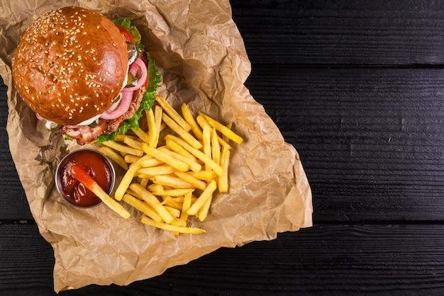 Alto ángulo para llevar hamburguesa de carne con papas fritas