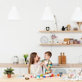Alto ángulo madre e hijo pintando huevos
