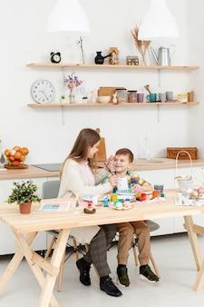 Alto ángulo mamá e hijo pintando huevos para pascua