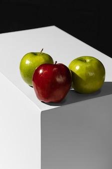 Alto ángulo de manzanas verdes y rojas en el podio