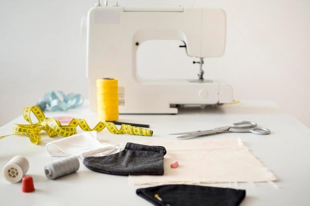 Alto ángulo de máquina de coser con cinta métrica y mascarillas
