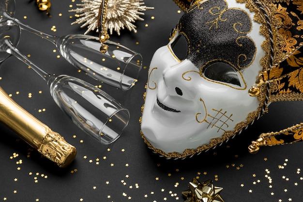 Alto ángulo de máscara para carnaval con purpurina y copas de champán.
