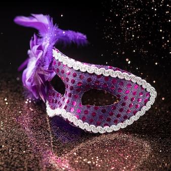 Alto ángulo de máscara de carnaval con purpurina y plumas.