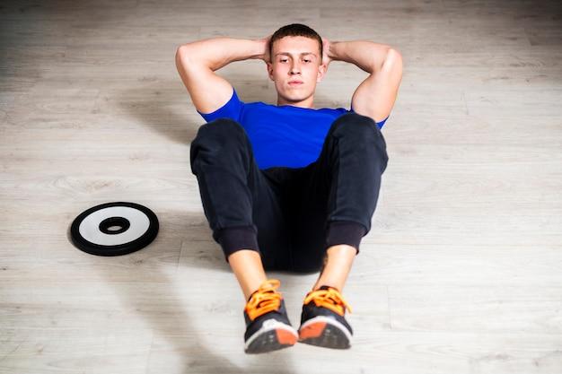 Alto ángulo masculino joven en el entrenamiento de gimnasio