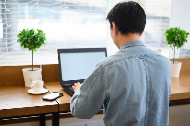 Alto ángulo masculino trabajando en la computadora portátil