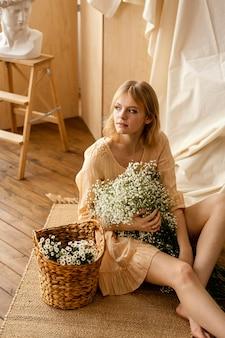 Alto ángulo de mujer con canasta de hermosas flores de primavera