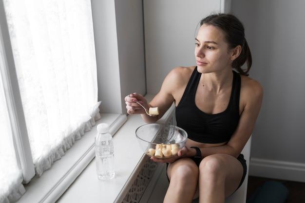 Alto ángulo de mujer comiendo y mirando por la ventana