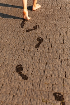 Alto ángulo de mujer dejando huellas mojadas en el suelo mientras camina