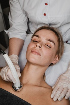 Alto ángulo de mujer joven recibiendo un tratamiento de belleza