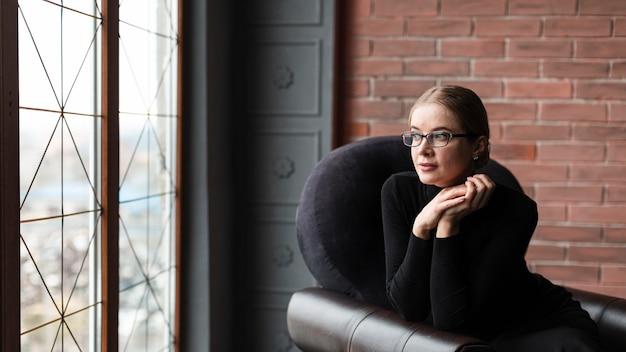Alto ángulo mujer joven sentada en el sofá