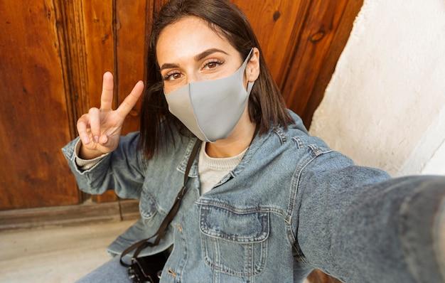 Alto ángulo de mujer con mascarilla tomando un selfie