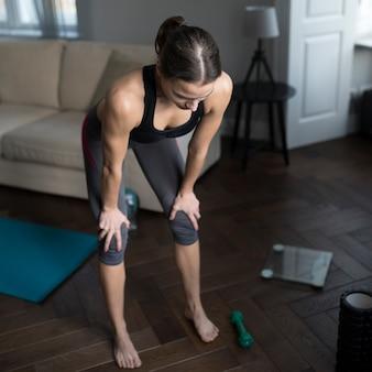 Alto ángulo de mujer recuperando el aliento después del ejercicio