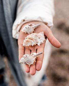 Alto ángulo de mujer sosteniendo conchas marinas en su mano