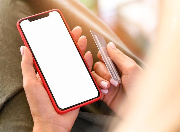Alto ángulo de mujer sosteniendo teléfono inteligente y tarjeta de crédito para cyber monday
