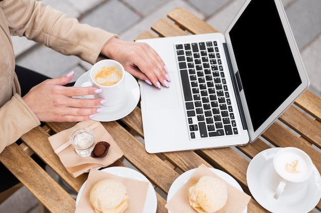 Alto ángulo de mujer trabajando en la computadora portátil al aire libre mientras almuerza