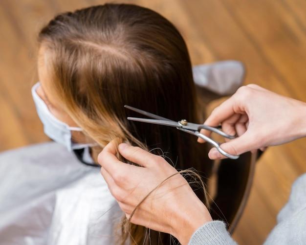 Alto ángulo de niña cortándose el pelo mientras usa máscara médica