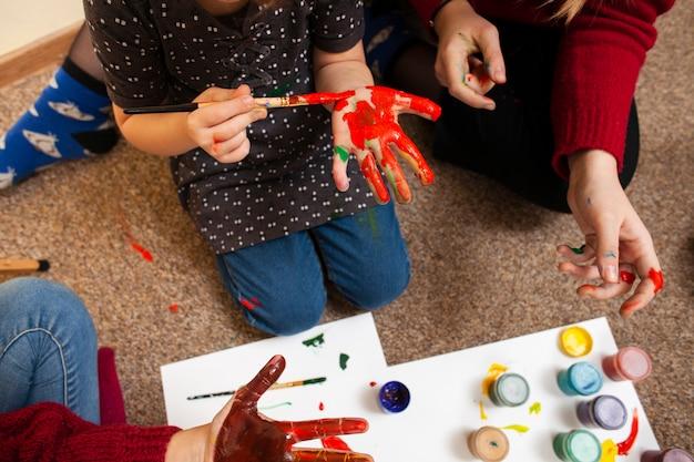 Alto ángulo de niña pintando su palma