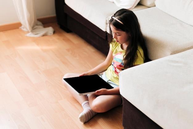 Alto ángulo niña sentada en el piso con tableta