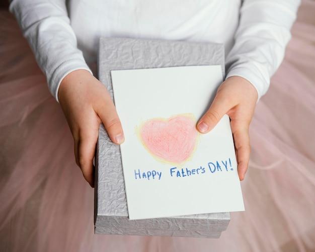 Alto ángulo de niña sosteniendo presente y tarjeta para el día del padre