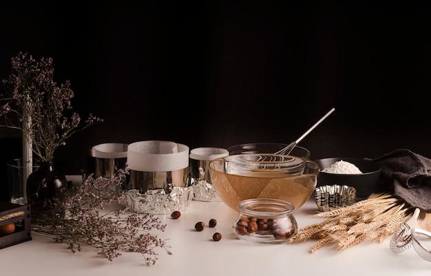 Alto ángulo de ollas y cuencos de cocina con castañas y trigo.