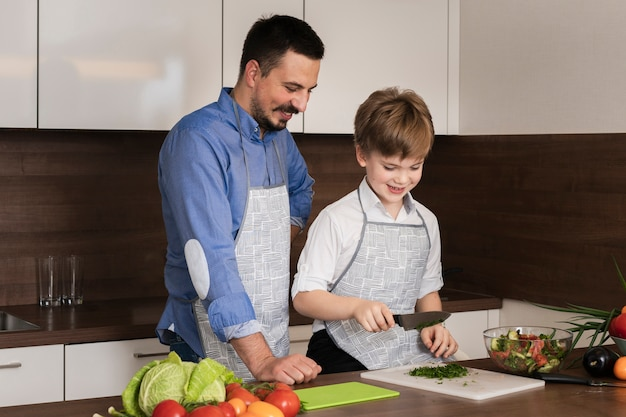 Alto ángulo padre e hijo cortando verduras