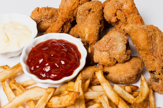 Alto ángulo de papas fritas y pollo frito.