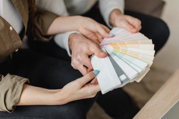 Alto ángulo de pareja haciendo planes para remodelar la casa juntos usando paleta de pintura