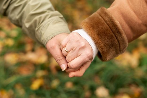 Alto ángulo pareja senior cogidos de la mano