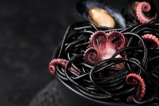Alto ángulo de pasta negra con calamares