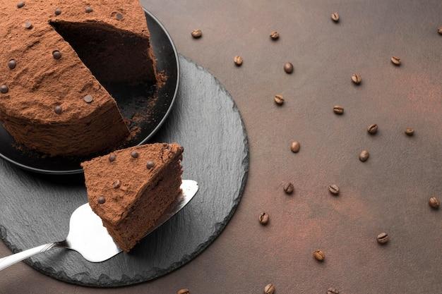 Alto ángulo de pastel de chocolate con granos de café.