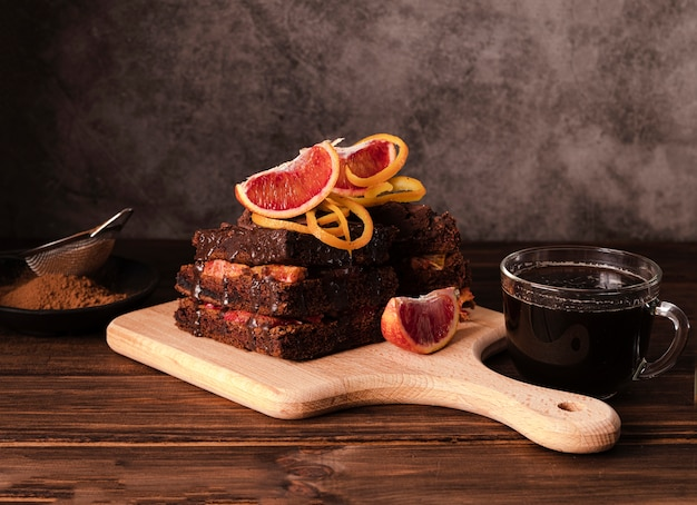 Alto ángulo de pastel de chocolate en la tabla de cortar con fruta