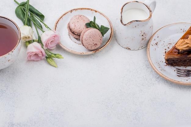 Alto ángulo de pastel con macarons y té