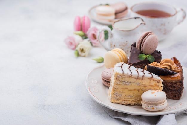 Alto ángulo de pastel en plato con macarons y espacio de copia