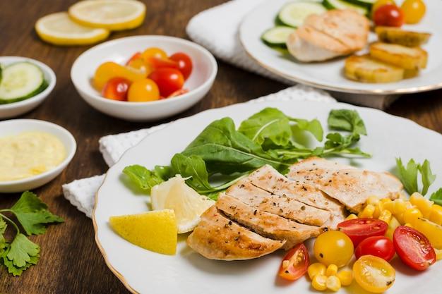 Alto ángulo de pechuga de pollo con variedad de verduras.