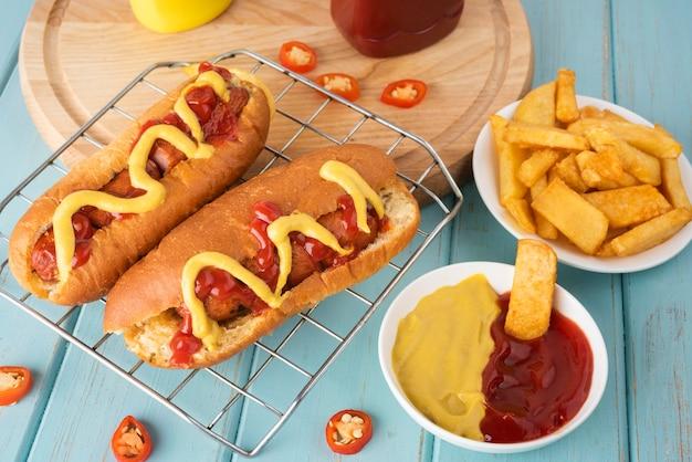 Alto ángulo de perros calientes con patatas y salsa de tomate y mostaza